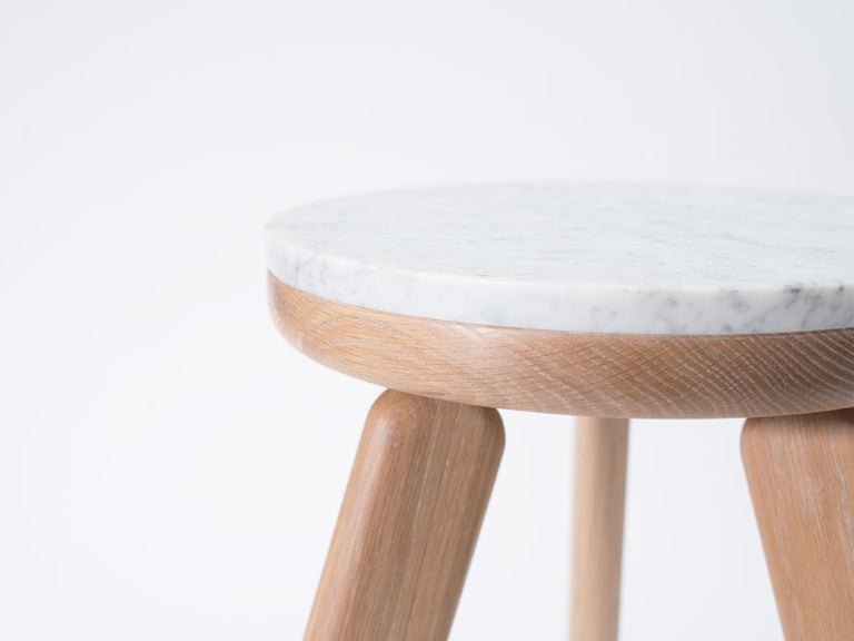 The Stele side table is handcrafted out of white oak and Carrara marble. Each table in the Stele series features a unique sculptural leg style. The Stele series utilizes and mix of stone and wood that compliments the properties of both materials;