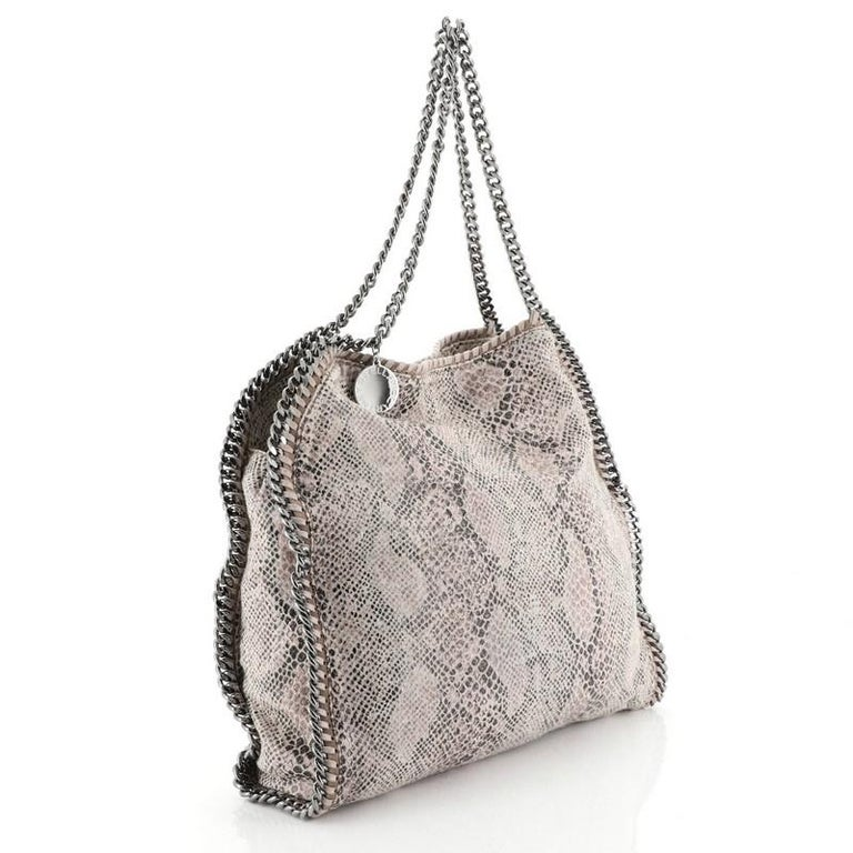 This Stella McCartney Falabella Tote Printed Canvas Small, crafted from pink metallic printed canvas, features chain link handles and trim, whipstitched edges, hanging logo disc, and gunmetal-tone hardware. Its magnetic snap closure opens to a black