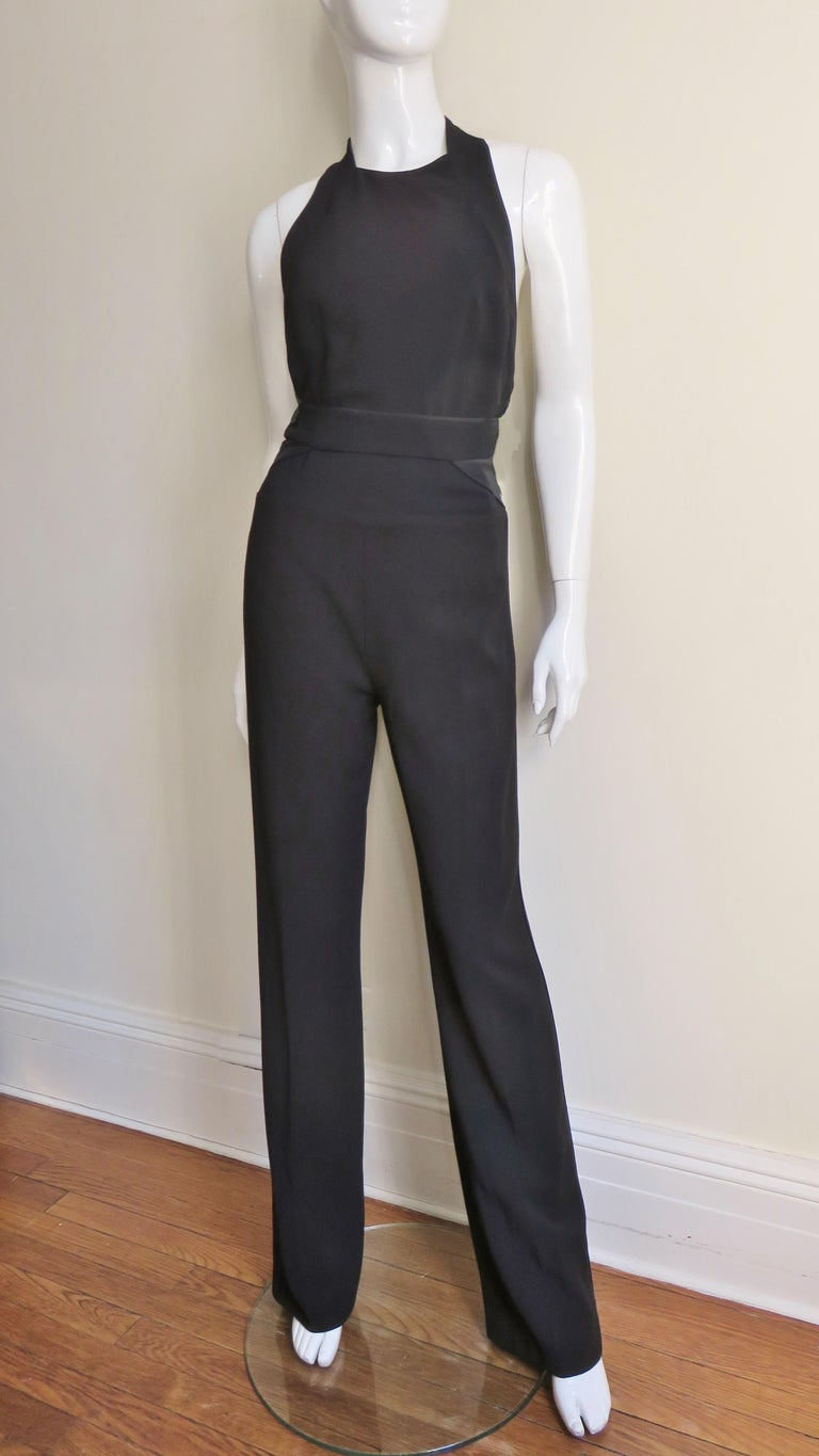 A fabulous black jumpsuit from Stella McCartney.  It has a crew neck, cut in shoulders, racerback and a band at the waist. The legs are straight and have matching piping along the outside of each leg.  It has a back zipper and is lined in black