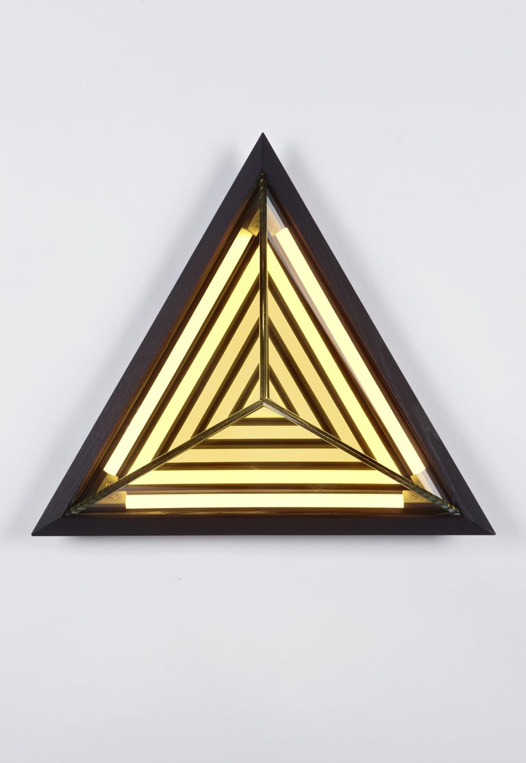 Inspired by his early work, this sconce is named after the painter Frank Stella. When illuminated, its half-mirrored glass diffuser reveals a series of nested geometric shapes. Stella creates the impression of infinite volume within a finite