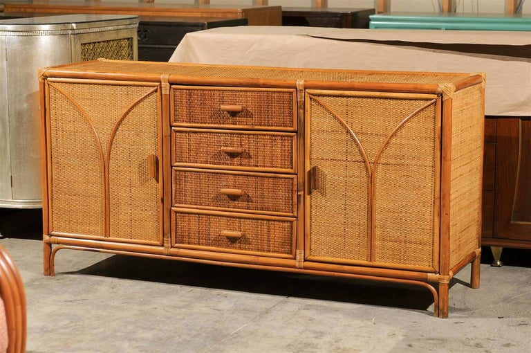 A beautiful rattan and cane cabinet or buffet, circa 1970s. Exceptionally crafted mahogany and rattan case construction with cane veneer and bamboo accents. The multipurpose design offers a center bank of drawers flanked by two open compartments.