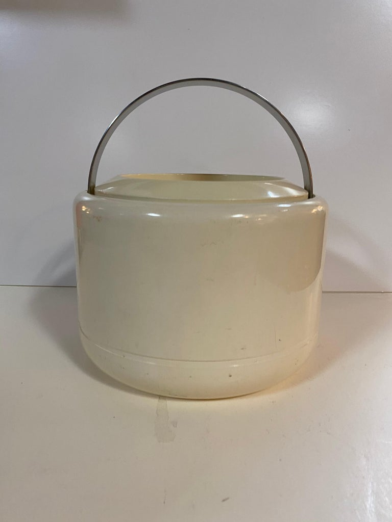A cream / off-white ice bucket by Erik Magnussen for Stelton. Made of plastic and features a brushed metal handle that folds down when not in use and a removable top with self-handle. Danish, circa 1960.  Marked on underside; Stelton Design, Erik