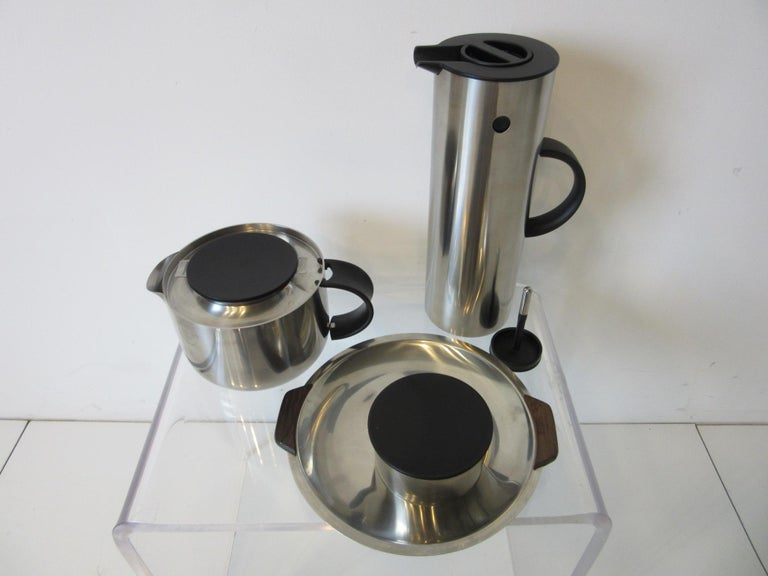 A four-piece set featuring a stainless steel water / coffee vacuum jug, with two tops, tea pot with strainer and lid, sugar bowl with lid and a small stainless tray having rosewood handles including the original bag all marked made in Denmark by