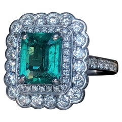 Step Cut Emerald with White Round Brilliant Cut Diamond Double Halo Ring