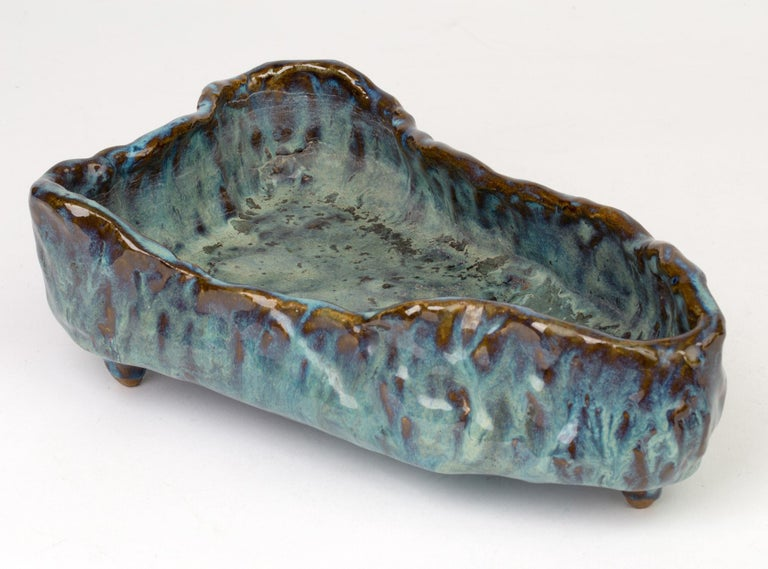 A stylish Brutalist sculptural form Studio Pottery open work bowl by Stephanie Kalan (1909-1978) probably dating 1953-1978. The bowl of elongated boat shape sits on a flat base and is formed in thick hand formed clay with a combed pattern natural