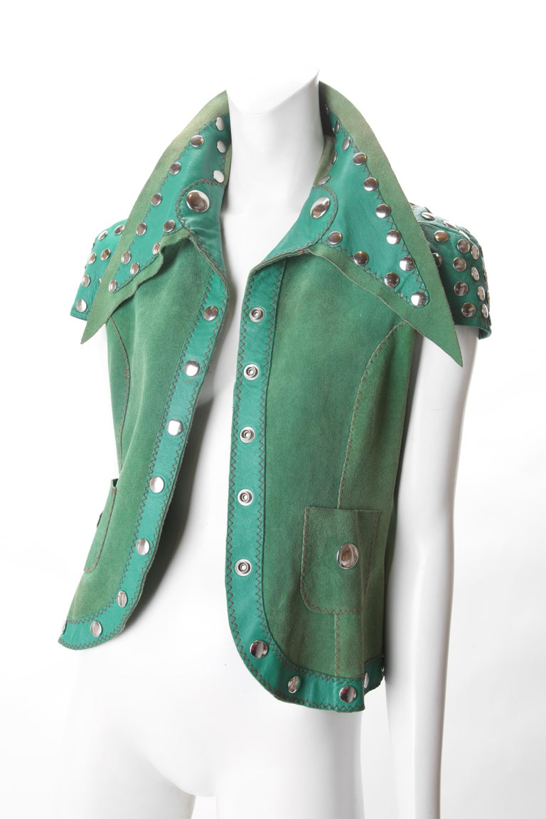 Stephen Burrows Green Suede & Leather Studded Vest, c.1970s. Stephen Burrows Suede Vest features contrasting leather accent detail at sleeves, exaggerated collar and lapel/hemline. Vest has silver studded buttons with Silver studs adorning the