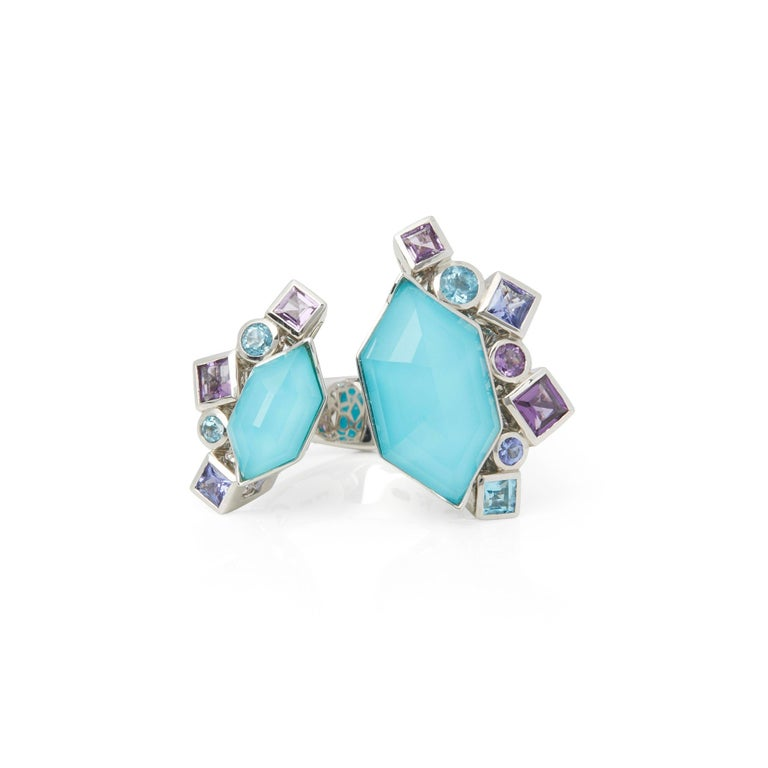 This Ring by Stephen Webster is from his Crystal Haze Gold Struck Collection and features Two Synthetic Turquoise set sections Totalling 6.65cts Surrounded with mixed cut Amethyst and Blue Topaz. Set in 18k White Gold with Signature Stephen Webster