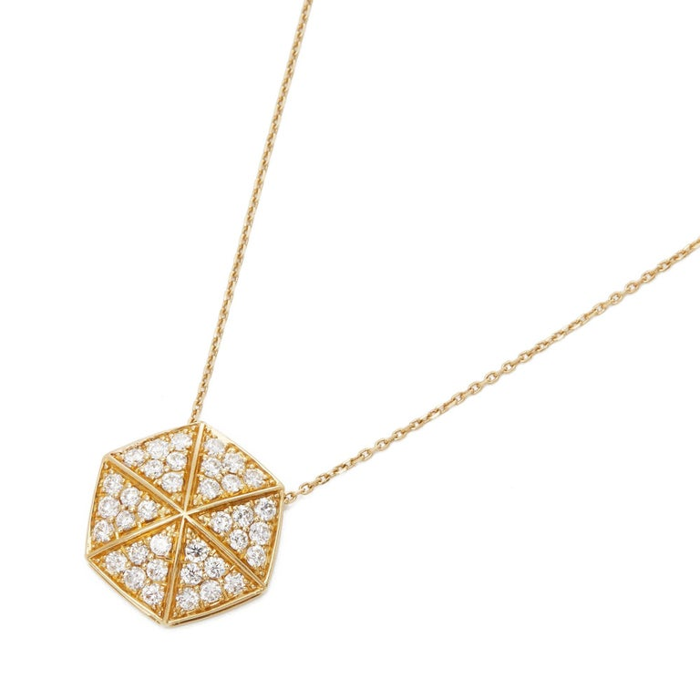 This Pendant by Stephen Webster is from his Deco Collection and features Six Pave Round Briliant Diamond set sections with a total of Thirty Six stones forming a Hexagonal shape. Set in 18k Yellow Gold with 41cm Trace Link Chain. Complete with Xupes