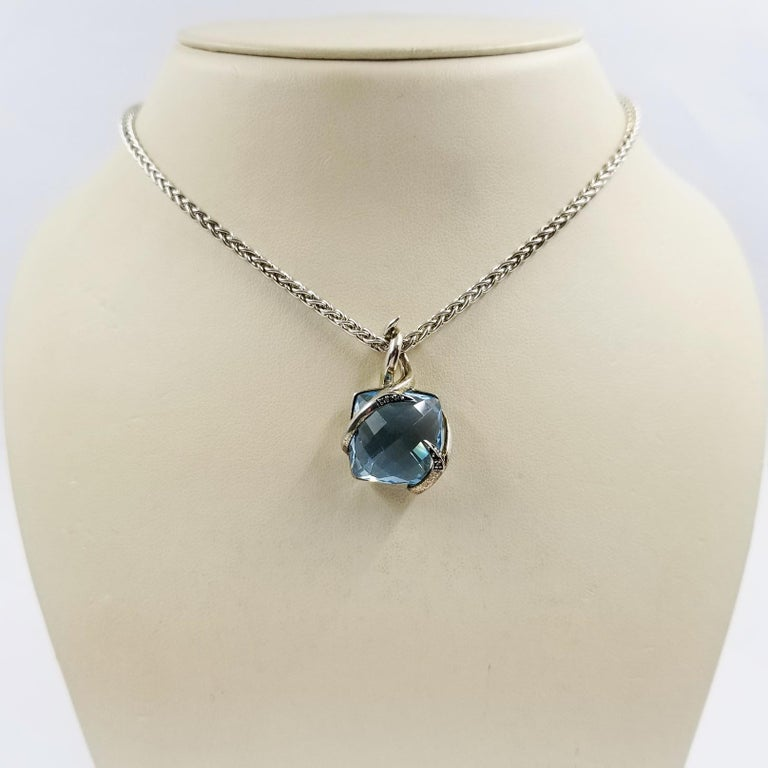 This simple pendant necklace is crafted in sterling silver by designer Stephen Webster. It features a 0.5 inch by 0.5 inch checkerboard cushion cut blue topaz center stone. The topaz is held in place by two wrapped diamond encrusted thorns. The