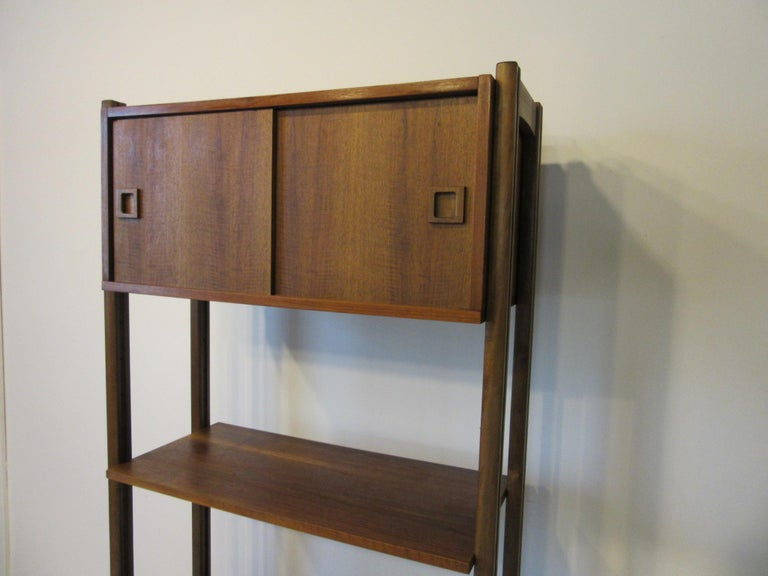 A walnut wall unit with upper two door storage cabinet, middle shelve for your stereo receiver and other equipment and lower area for the turntable and a record cabinet having five slots sits at the base. All the pieces are adjustable so you can