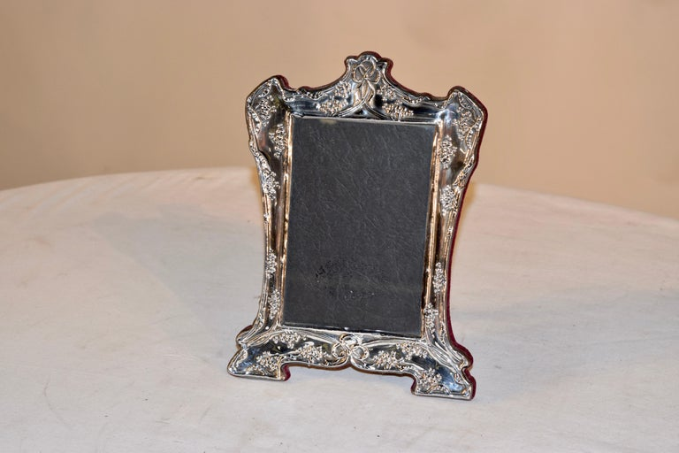 Lovely Art Nouveau picture frame with velvet covered back and stand. The frame has a graceful shape and is decorated with florals. Marked sterling at the bottom of the frame.