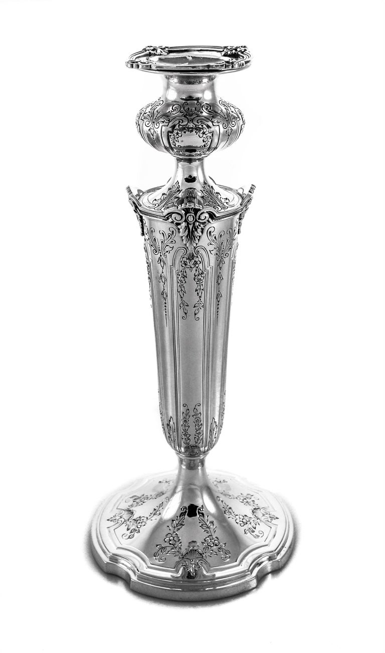 These sterling silver candlesticks have etched flowers and vines decorating the base and all around the top. Notice the scalloped base and the matching scalloped bobeche. Towards the top of the candlestick the silver juts out to form little corners.