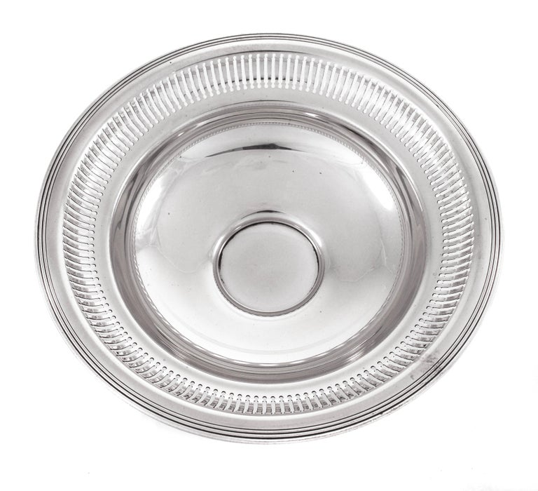The bowl stands on a pedestal and is not weighted. It was made by the Gorham Company of Providence, Rhode Island. It has a series of cutouts going around the entire top. The cutouts are approximately one inch long and have a circular design both on