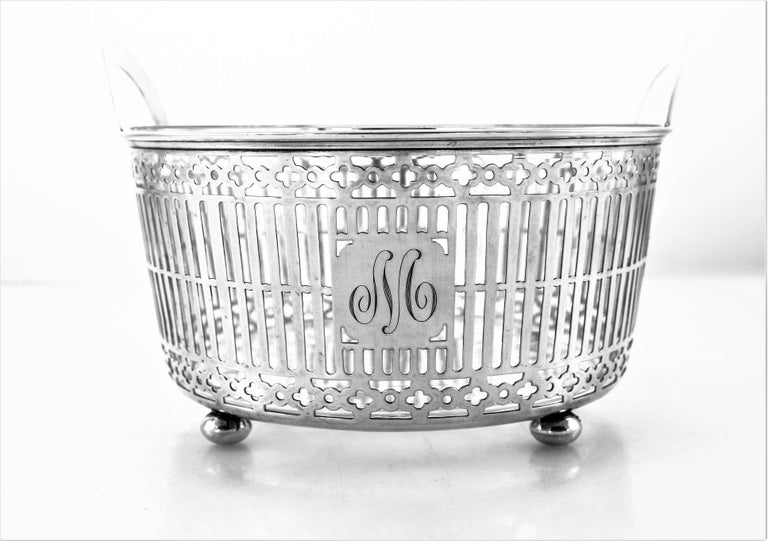 This sterling silver ice bucket has a lattice pattern going around the entire circumference. On each end there is a semi-circular handle to hold and pass it around. It stands on four ball-feet that props it off the surface. The crystal liner comes