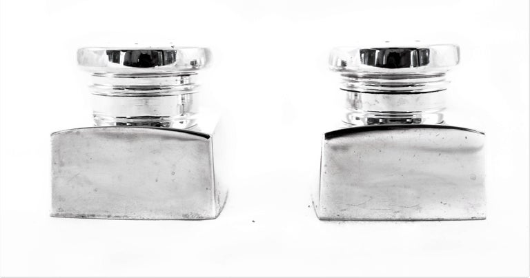 Uber-modern and uber-chic, this pair of salt and pepper shakers has that midcentury look that is so popular. A square shape body topped with a round cover. There are no etchings or decoration on them, just the clean look of sterling silver.