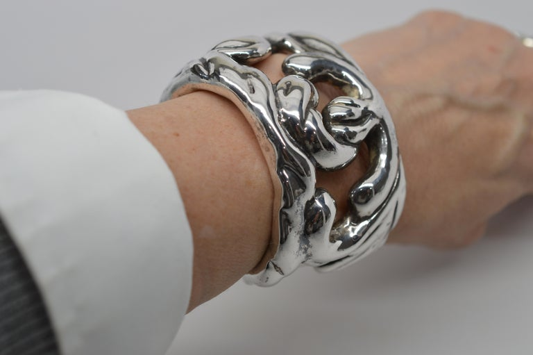 Abstract in design, substantial in construction, this bold cuff style bracelet is plated in Sterling Silver and marked by its maker. Has toning and slight tarnish on finish. Slip on style, measures 2-1/4 x 1-3/4 inches with a circumference of 6-1/2