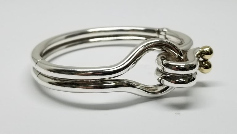 Sterling Silver and 14k gold solid tube Designer Bracelet, made of solid 4mm wire formed to a beautiful knot design with 2 5mm 14k yellow gold balls.  the clasp and hinge are very strong. Measurements; inside diameter 2 1/4 inches and inside top to