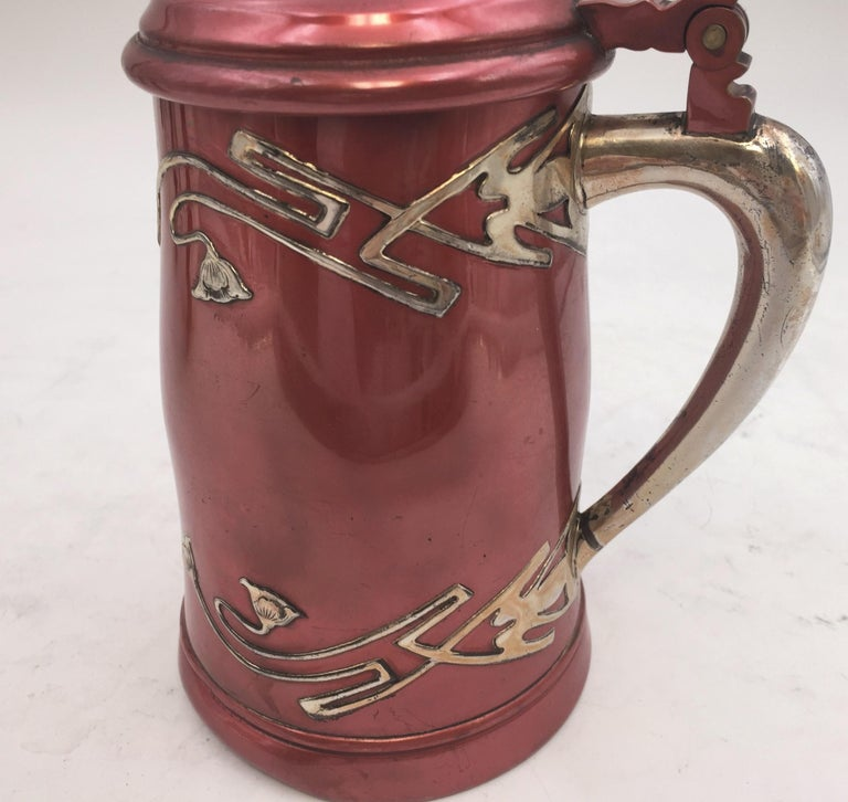 Early 20th century metal tankard with inlaid sterling silver floral design and handle by W. J. Braitsch & Co , an American silversmith based in Providence, RI. Measuring 7 1/4'' in height and 5'' in length. Weighs 19 ozt. Bearing hallmarks as