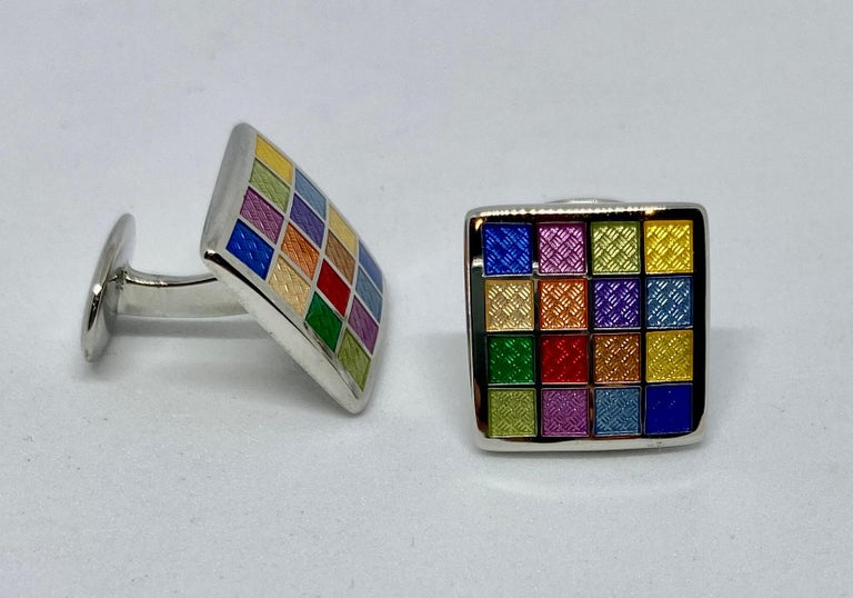 A colorful pair of cufflinks featuring enamel on solid sterling silver.  The faces measure 16.6mm square and feature a range of brightly colored enamel squares upon sterling silver. Together the cufflinks weigh 13.63 grams.  The cufflinks are