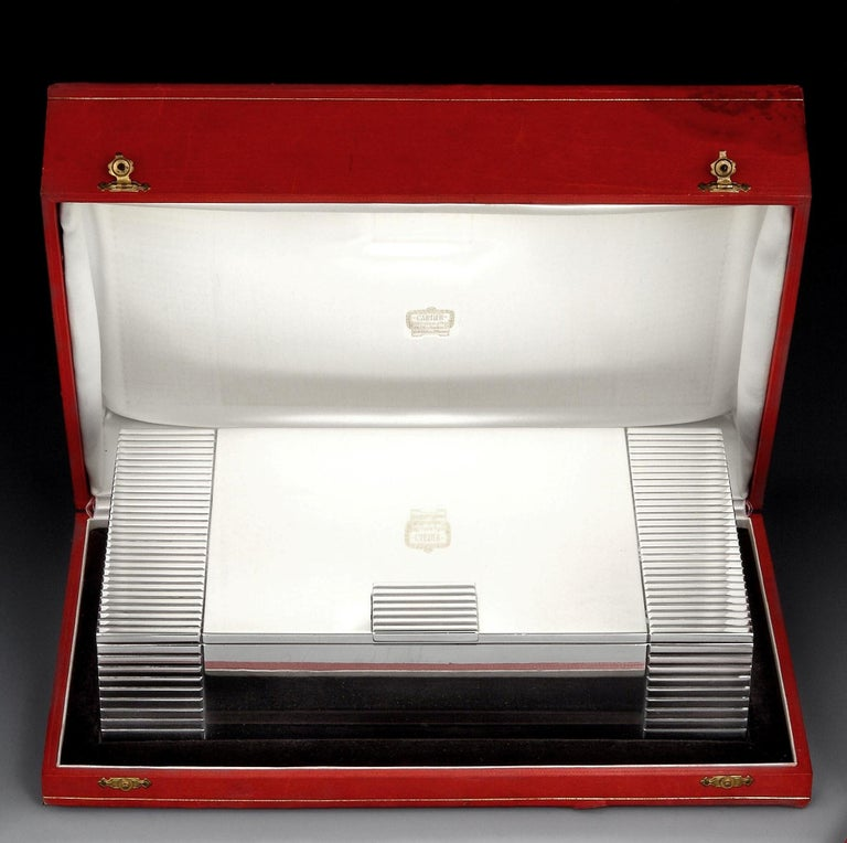 Cartier, Paris  A magnificent and generous sterling silver Art Deco cigar box of rectangular form, with a thick reeded border left and right, and a similarly designed thumbpiece. The interior of the box is cedar lined with a single, central