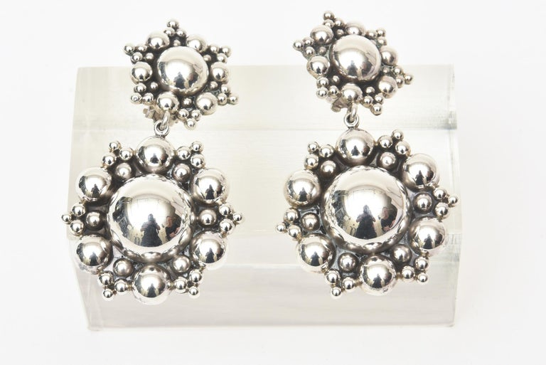 These stunning and dramatic never worn sterling silver dangle clip on earrings were originally from Neiman Marcus from the 80's. They have a great presence and will be a statement on your ears. They have a great cluster ball form at the top and