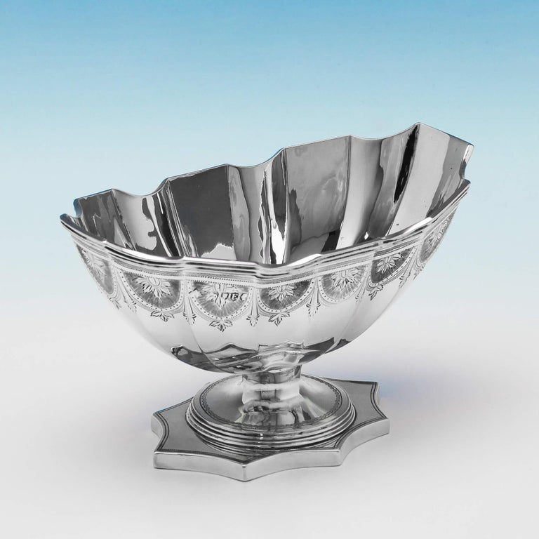 Hallmarked in London in 1880 by A. B. Savoury & Sons, this attractive, Victorian, antique sterling silver bowl, features bright cut engraved decoration, shaped sides, and stands on a scalloped pedestal foot. The bowl measures: 3.5 inches (8.5cm)