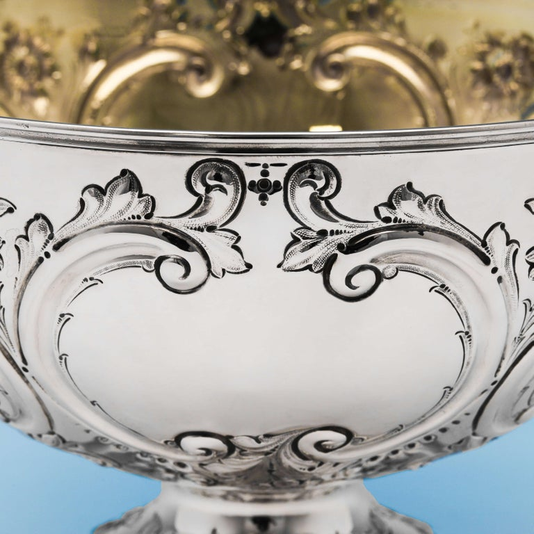 Hallmarked in London, in 1889 by Barnards, this attractive, Victorian, antique sterling silver bowl, features floral and scroll chased decoration throughout, and a gilt interior. The bowl stands on a pedestal foot and measures 7.5 inches (19cm) in