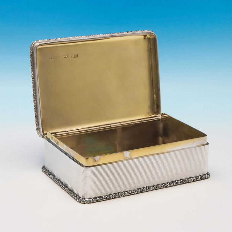 Hallmarked in London in 1911 by D. & J. Wellby, this exceptional, Antique, sterling silver table snuff box, is rectangular in shape, and features a cast border, gilt interior, and engine turned decoration. The snuff box measures 2.25