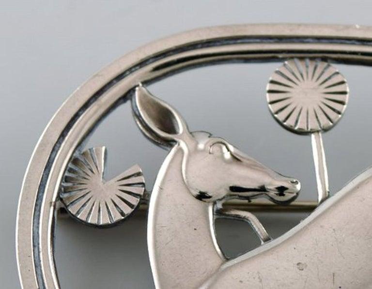 Sterling silver brooch by Georg Jensen. Design number 256. Deer motif. Stamped. In very good condition. Measures: 4.6 x 3.7 cm.