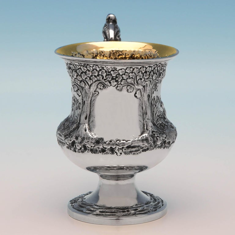 Hallmarked in London in 1839 by Charles Lias, this charming antique, Victorian, sterling silver christening mug has a concave body chased with a scene of pheasants in foliage. It stands on a pedestal base, with an acanthus scroll handle and a gilt