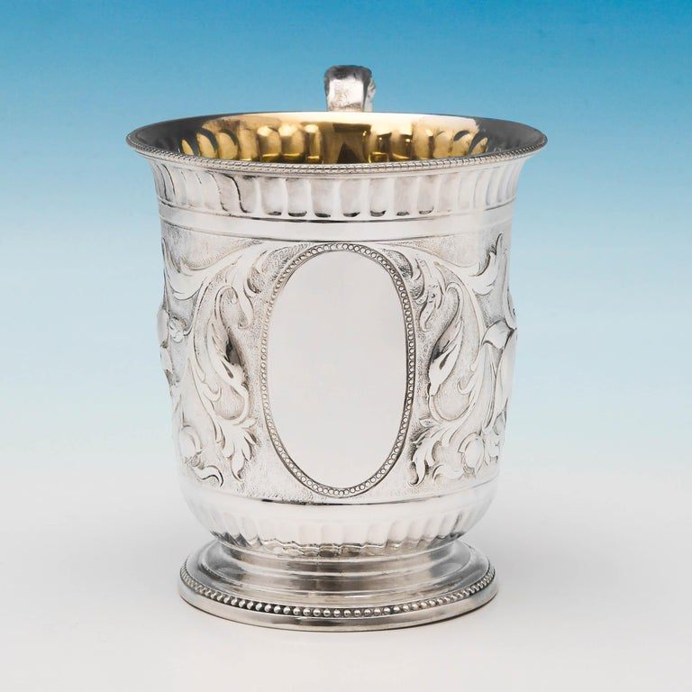 Hallmarked in London in 1867 by Samuel Smily, this striking, Victorian, antique, sterling silver Christening mug, features chased naturalistic decoration, an acanthus detailed scroll handle, and a gilt interior. The christening mug measures: 3.75