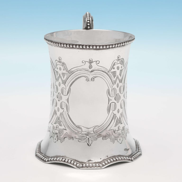 Hallmarked in London in 1858 by Robert Hennell II, this attractive, Victorian, antique sterling silver Christening mug, features bright cut engraved decoration throughout, bead borders and an unusual shaped base. The christening mug measures: 4