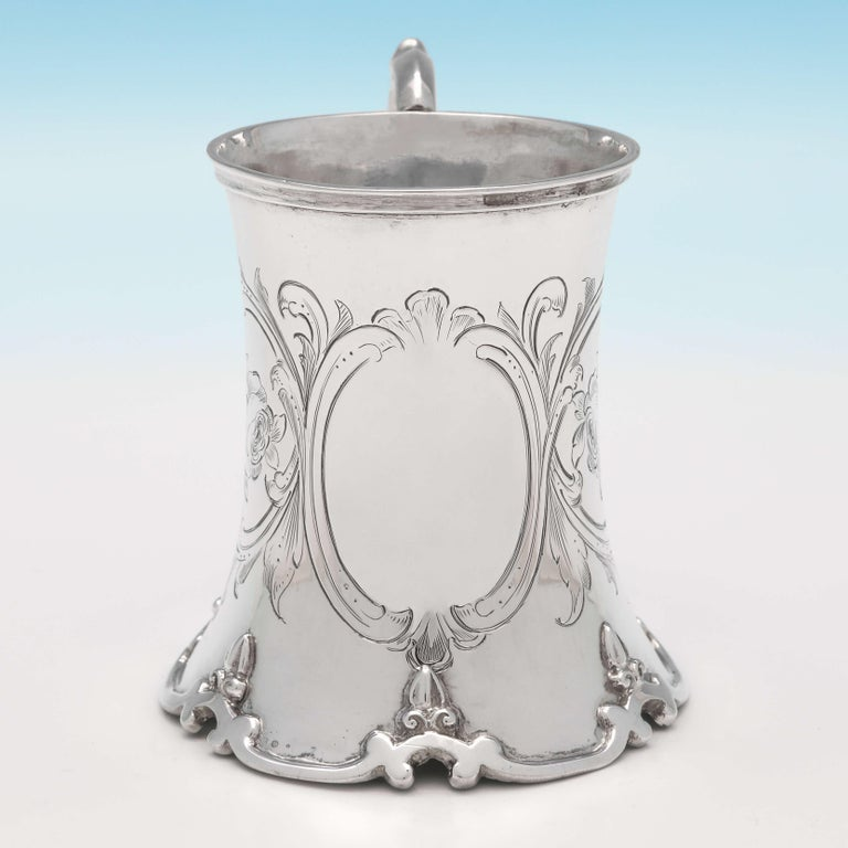 Hallmarked in London in 1852 by Robert Hennell IV, this elegant, Victorian, antique sterling silver Christening mug, has concave shaping with a scroll base, engraved decoration, a scroll handle and a gilt interior. The christening mug measures