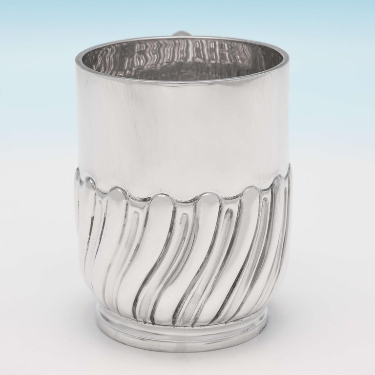 Hallmarked in London in 1898 by Jackson & Fullerton, this handsome, Victorian, antique sterling silver Christening mug, features swirled half fluted decoration and a plain loop handle. The christening mug measures 3.25