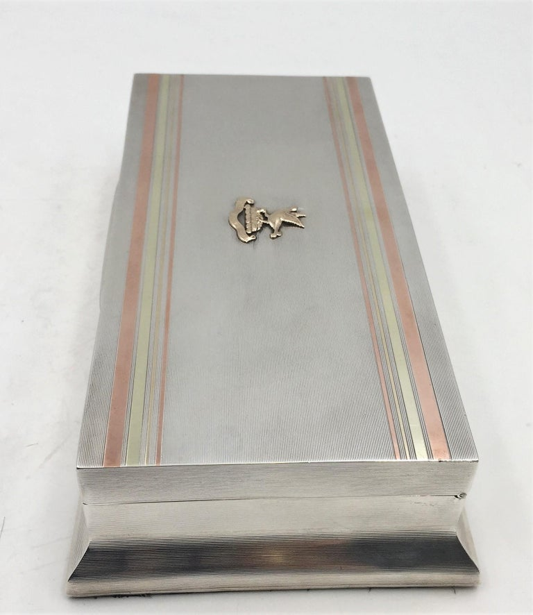 Exquisite English silver cigar box with gilt crest and four-toned gilt inserts on the cover, a wood lined interior, adjustable compartments, and a leather-covered base. It dates from 1929 and is by William Frederick Wright, a London-based