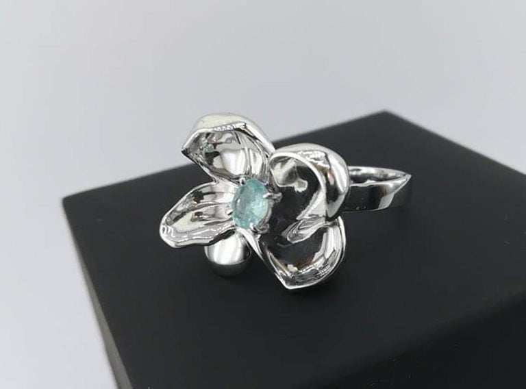 This Magnolia Flower contemporary cocktail ring is in sterling silver with oval copper bearing Paraiba tourmaline, 0.28 carats. The water-surface of the gem multiplies the light, mirroring on the golden petals. The weight is 8.5 gram, ring has 4