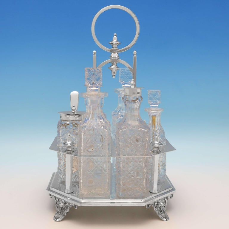 Hallmarked in London in 1896 by Charles Boyton II, this stylish, Victorian, antique sterling silver cruet set, comprises two oil bottles, two pepper pots, a cayenne pepper pot, and a mustard pot, all with hobnail cut glass, and all set in an