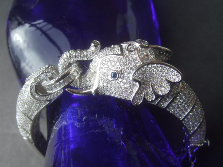 Exquisite sterling silver crystal encrusted hinged elephant bangle  The majestic elephant figure is embellished with intricate rows of contiguous tiny diamante crystals  The elephant's eyes are distinguished with tiny sapphire blue color crystals.
