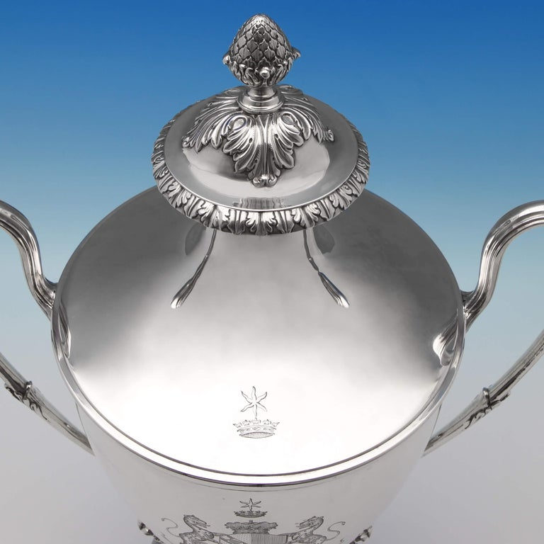 Hallmarked in London in 1773 by Charles Wright, this striking, antique George III, sterling silver cup and cover, features reed detailed loop handles and applied acanthus decoration. The cup bears an original engraved coat of arms for John Frederick