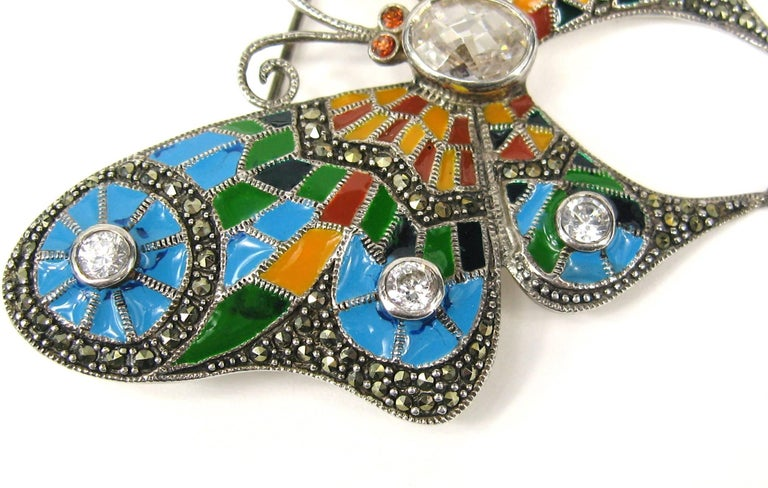 Stunning Sterling Silver Enameled Butterfly Brooch. Colors are Oranges, Blues and greens with a bit of black. This Measures 2.85 in x 2.44 in wide. Marcasites scattered throughout the Brooch and a large faceted crystal in the center. Bezel set