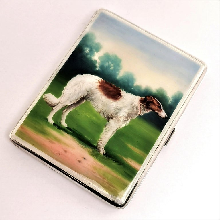 A gorgeous vintage solid silver and enamel cigarette case featuring a beautiful enamel image of a dog on the cover. The image is created in deep, rich colors and with a wonderful attention to detail. The images shows a hunting dog, possibly a Borzoi