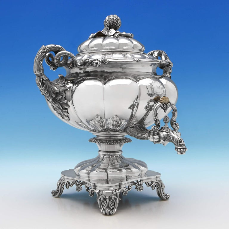 Hallmarked in London in 1828 by Barnards, this impressive antique, George IV, sterling silver five-piece tea and coffee service is in the famous Barnard's Melon design and features shell feet, pumpkin finials, and an engraved coat of arms to the
