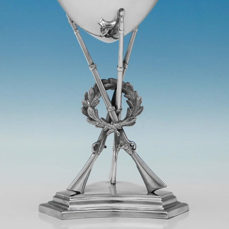 Hallmarked in London in 1863 by George Angell, this fine antique, Victorian, sterling silver goblet would make an ideal presentation piece. It stands on a stepped pedestal base, with three rifles and a wreath forming the stem. It measures 9