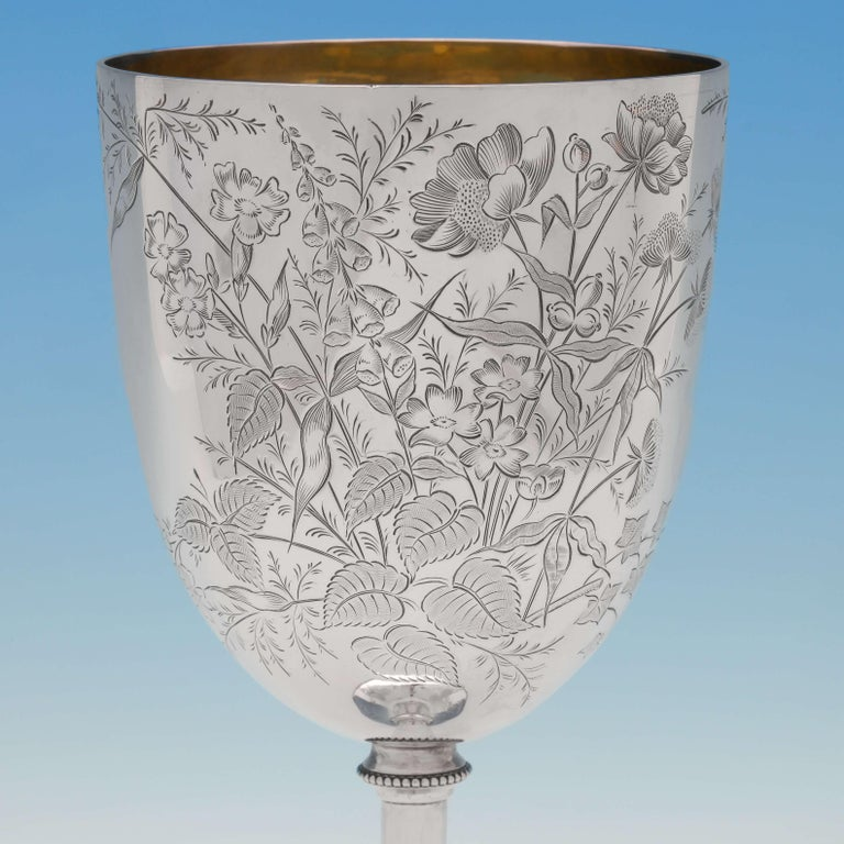 Hallmarked in Sheffield in 1887 by W. W. Harrison, this attractive, large, Victorian, antique, sterling silver goblet, features naturalistic engraving throughout, a bead border, and a gilt interior. The goblet measures 9