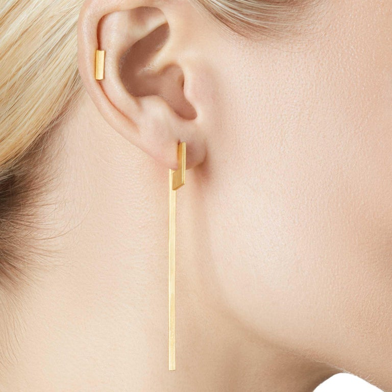 Unfinishing Line collection exudes minimalism and precision with its smooth lines and angles.  Detailed with a perspective studs and long swinging bar structure with a matt brushed finish.  Each part of this pair of earring can be separated for