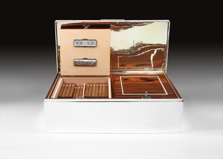 A magnificently large, Sterling silver cigar box of gigantic proportions, the heavy gauge, double walled body with hinged lid has been relined in kiln-dried cedar, and features two ebene-de-macassar veneered doors, each with decorative silver