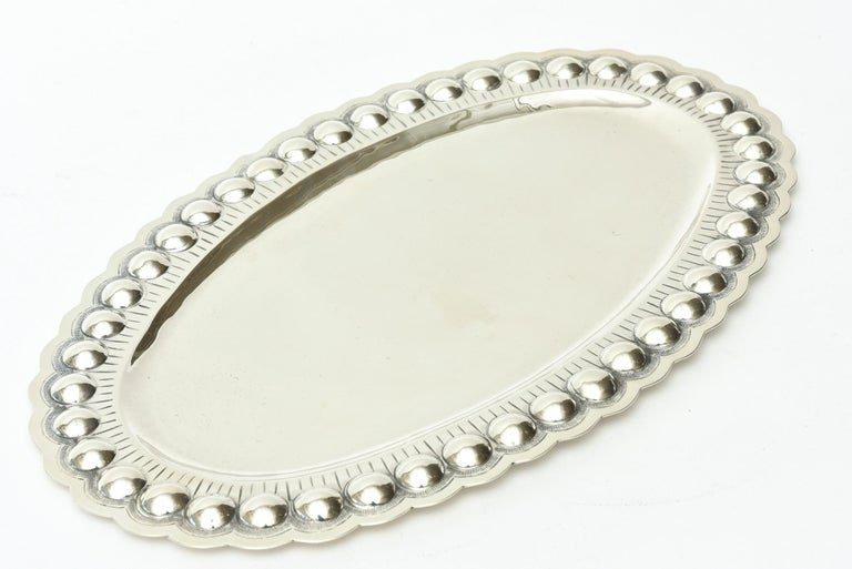 This lovely embellished Mid-Century Modern sterling silver tray is oval. The applications are varied for a multitude of uses as barware, serving and or holding towels for your bathroom. It is hallmarked 925, 1000 Sterling. It is from the 1950s. The