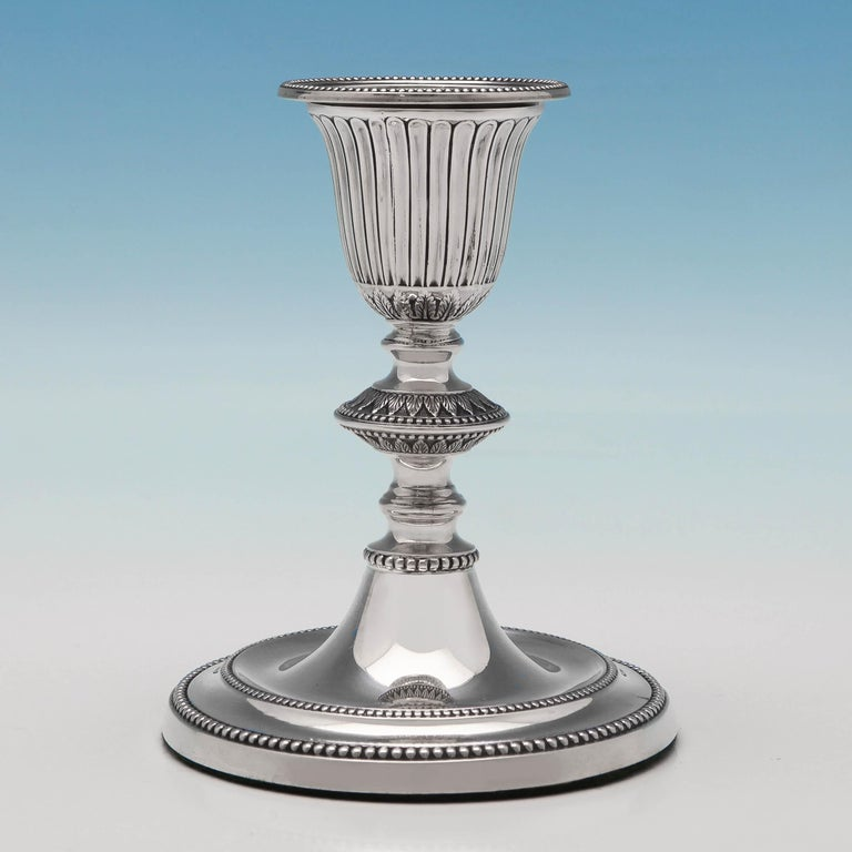 Hallmarked in Sheffield in 1886 by James Kebberling Bembridge, this attractive pair of Victorian antique, sterling silver candlesticks, feature bead borders, fluted decoration, acanthus detailing, and removable sconces. Each candlestick measures