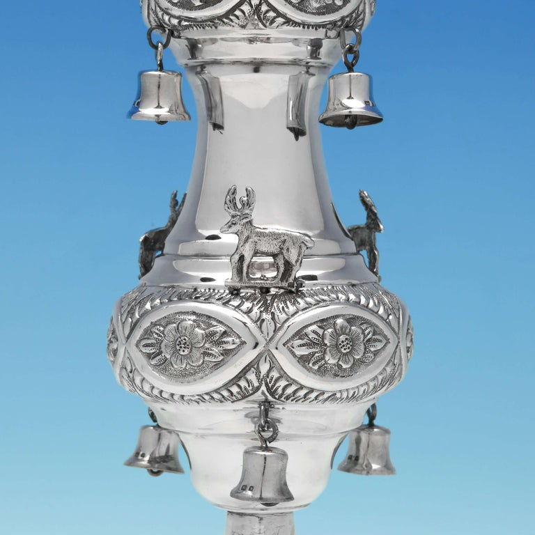 Hallmarked in London in 1920 by Maurice Salkind, this impressive pair of sterling silver Rimonim feature floral chasing, eagle finials, deer, hanging bells and beaded bases. The handles have been engraved with Hebrew script. Each Rimonim stands