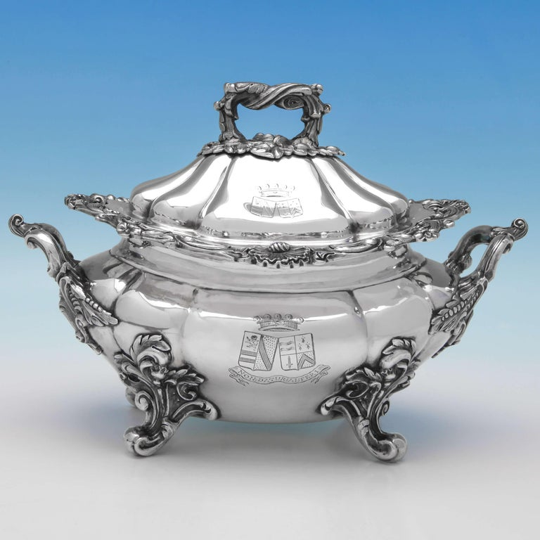 Hallmarked in London in 1842 by John Figg, this extraordinary pair of Victorian, antique sterling silver Sauce Tureens, feature scroll borders, ornate handles and feet, and engraved crests and mottos. Each sauce tureen measures 7